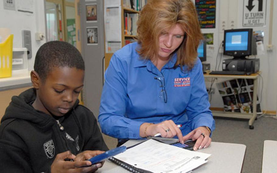 After approving his loan request to buy a used car, Sandra Campbell of Service Credit Union helps Willis Davis crunch numbers as they try to improve his credit rating. It was all part of a yearlong seventh-grade project on personal financing at Kaiserslautern Middle School.
