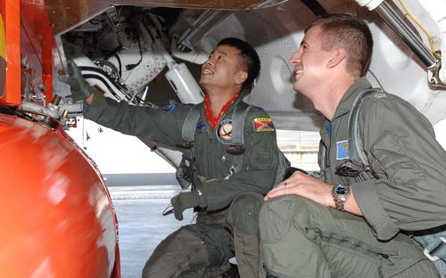 South Korean air force Lt. Col. Jeong Geun-hwa, left, and Navy Lt. Joshua Filbey examine the T-50 training aircraft at a South Korea base in Sancheon recently. FIlbey and three other flyers from the U.S. Naval Test Pilot School flew the advanced jet trainer this past week. The aircraft is considered a modern stepping stone to current and future jet fighters. Filbey and Marine Maj. Jonathan Ohman are writing technical reports on the aircraft as part of their graduation from the test pilot school.