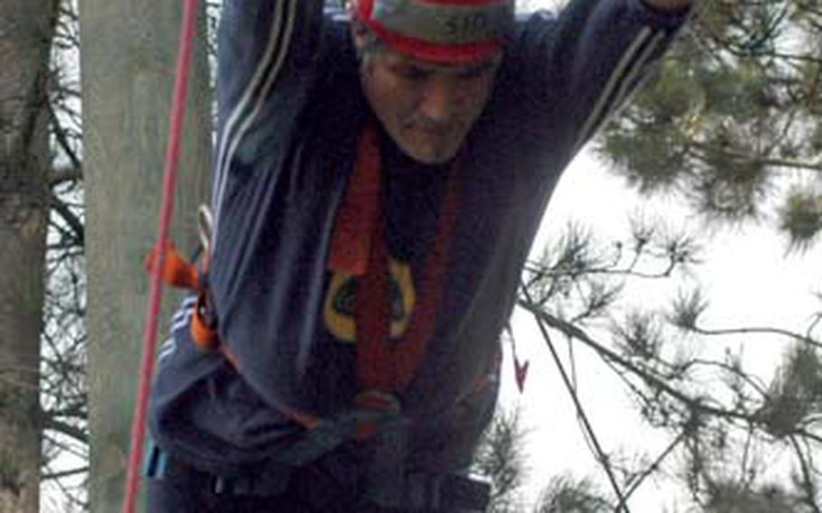 """Sid Boardman, a civilian employee of Stars and Stripes at RAF Mildenhall, makes the """"leap of faith"""" on the ropes course at the base."""