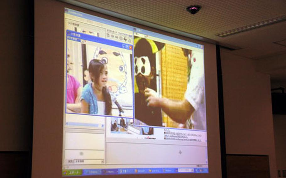 On the screen, 10-year-old Darryl Torres, a fifth-grader at Kadena Elementary School, guides a student from Shimoji Elementary School on Japan's Miyako Island through a game of fukuwarai on Tuesday. The two classrooms participated in a video teleconference from both the Okinawa Prefectural Comprehensive Education Center in Okinawa City and Miyako Island.