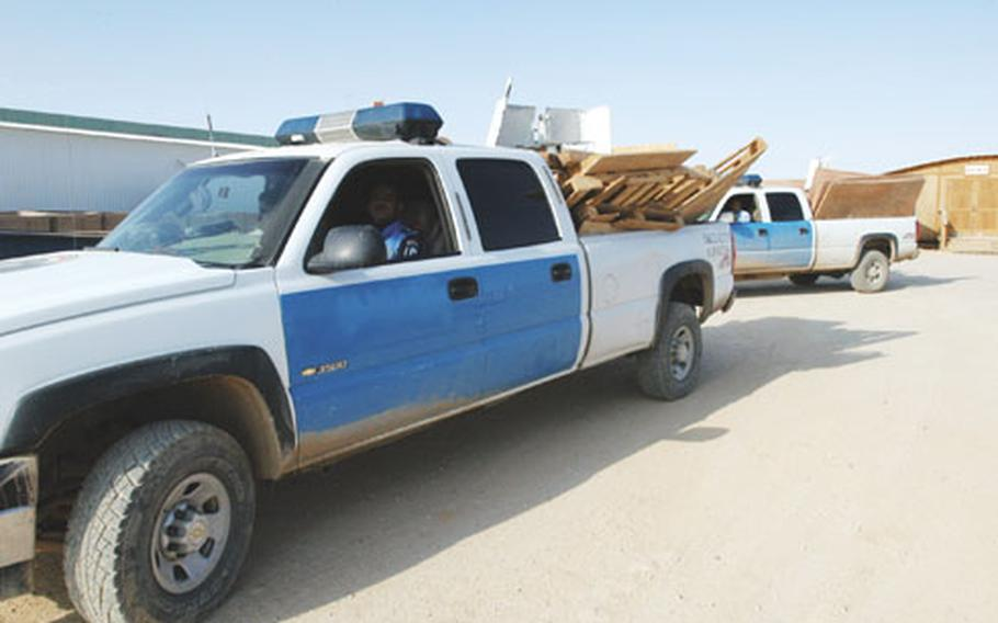Iraqi police drive away from Camp Korean Village, Iraq, with two truckloads of wood. Marines form the 2nd Battalion, 25th Marine Regiment donated the wood to the city of Rutbah for the construction of school desks.