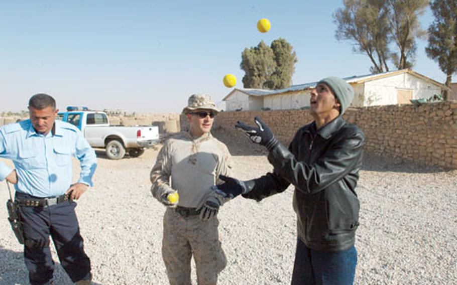 Capt. Paul Greenberg, 2nd Battalion, 25th Marine Regiment, teaches Iraqi policemen Thama Mahaber Salah Kubasi, right, and Abdullah Zaik, left, to juggle while waiting for a patrol in Rutbah, Iraq.