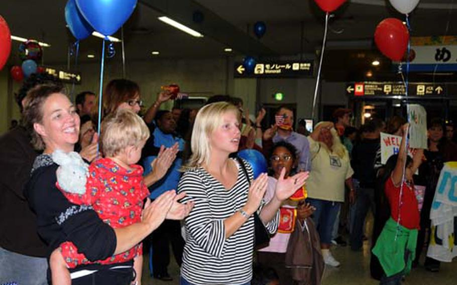 Teachers cheer as Marines, retuning from a deployment to Afghanistan, walk out of the Naha Airport baggage terminal Wednesday evening. The teachers, most from Bechtel Elementary on Camp McTureous, volunteered to provide individual greetings for the single troops who had no family on the island to welcome them home.