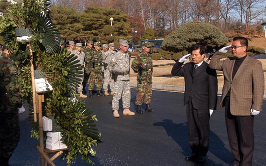 """Two of the Joint Security Area's """"Old Boys"""" -- soldiers who served along the border separating the two Koreas -- salute a wreath honoring Jang Moung-ki Friday near Conference Row in Panmunjeom. Jang was killed 24 years ago after North Korean soldiers pursued a Soviet defector across the military demarcation line."""
