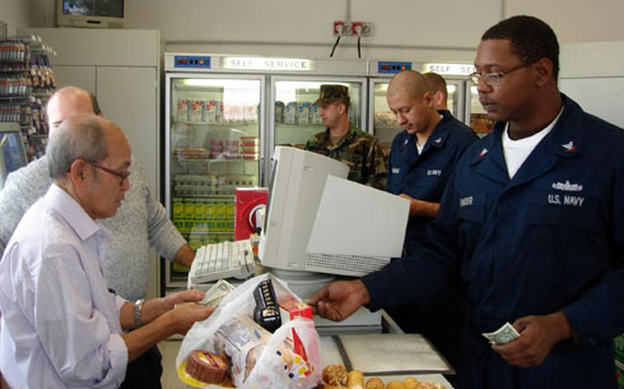 Petty Officer 3rd Class Antisuan Ponder is the first sailor to buy items from the new Navy Exchange mini-mart in Gaeta, Italy, which opened Monday.