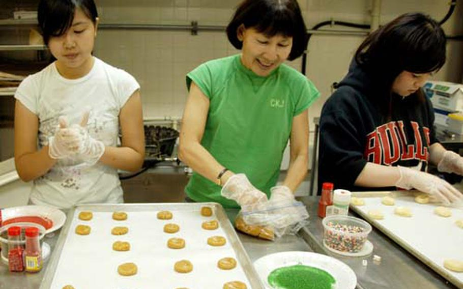 Kelly Kaneshiro, 14, left, a freshman at Kadena High School, and her mother, Arlene, roll out sugar cookie dough. Airi Tanahara, 20, right, a first-year student at Nikkei Business College, pitched in to help. Volunteers baked about 24,000 cookies this week for the annual holiday cookie drive at Kadena Air Base, Okinawa for single servicemembers.