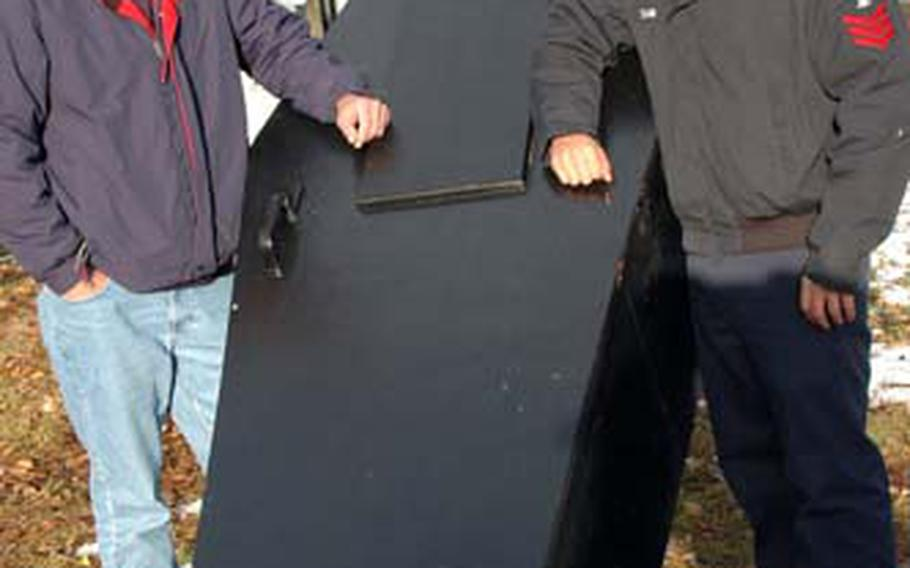 Naval Air Facility Misawa safety manager Jeffrey Wilson, left, and Petty Officer 1st Class Harry Turnland, an information systems technician, pose at a coffin that's part of a new holiday DUI awareness display near the front gate at Misawa Air Base, Japan.