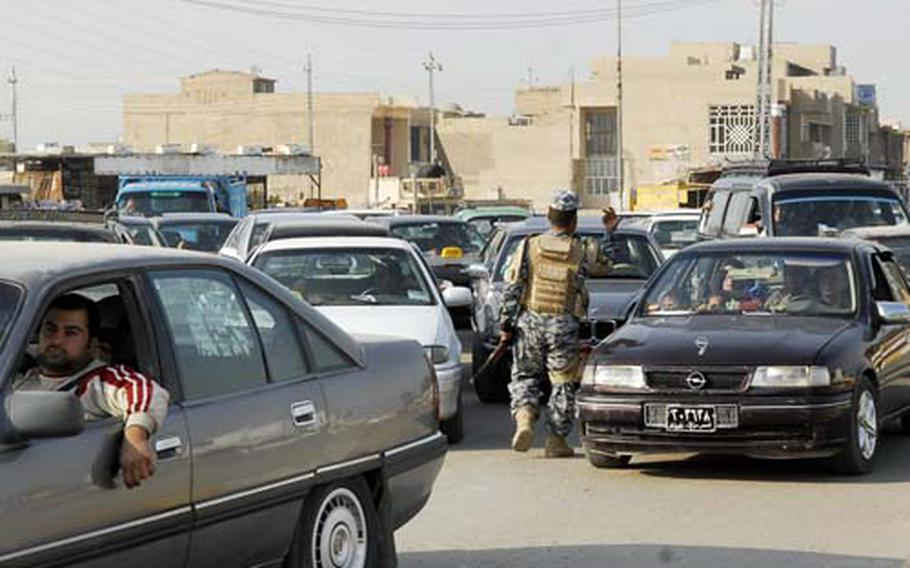 An Iraqi National Police officer directs gridlocked traffic at a checkpoint outside a south Baghdad market. Extra security measures in some neighborhoods are credited with reducing violence.