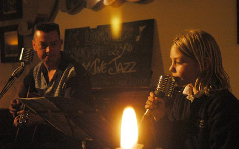"""Lana Bruce, right, belts out her own rendition of Amy Winehouse's """"Rehab"""" as her dad, Jason, plays guitar. Jason Bruce plays each week at The Chequers, left, a hip little place in Fordham. Lana sits in for a few songs every now and then."""