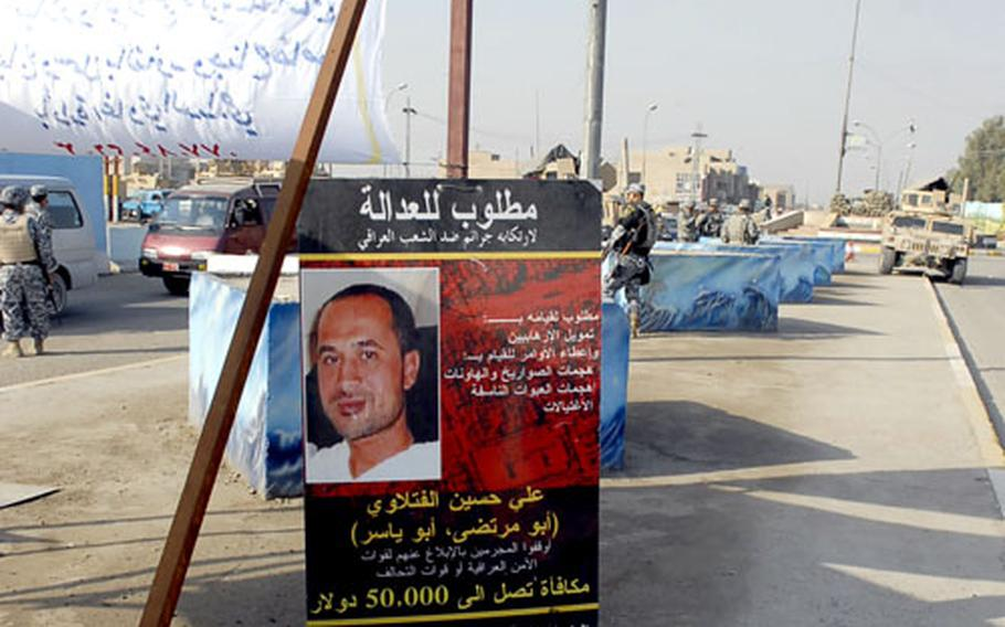 A wanted poster is displayed at a market checkpoint in Baghdad's Abu T'Shir neighborhood. Security officials credit the poster campaign with driving insurgents underground.