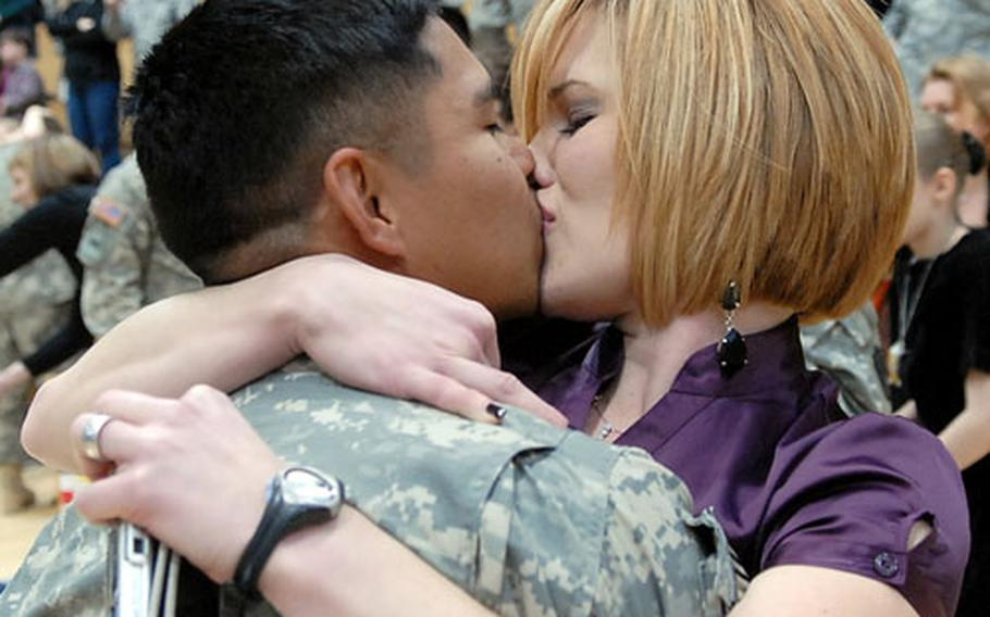 Sgt. 1st Class Melvin Bautista gets a big kiss from wife Katie following his return to Wiesbaden Army Airfield Tuesday afternoon.