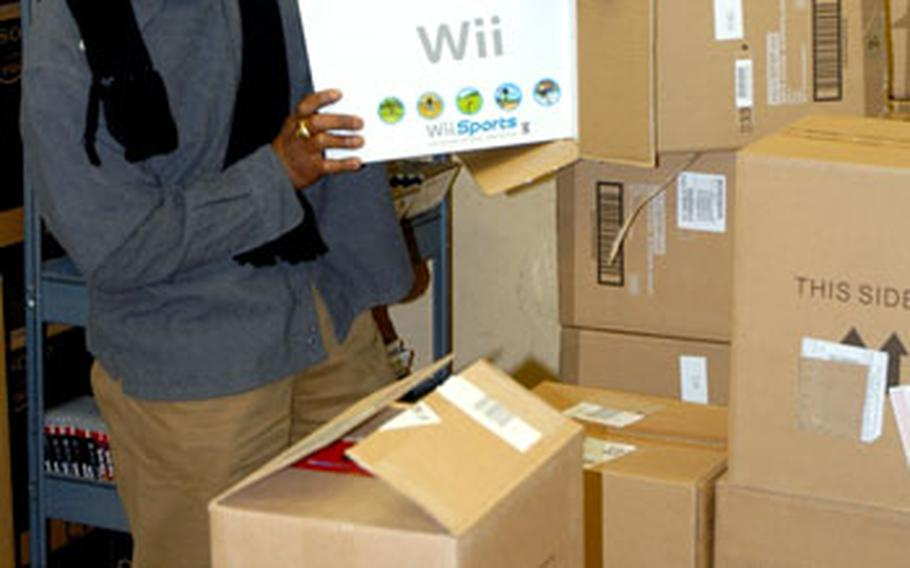 """Dwight Johnson, a 10-year Army and Air Force Exchange Service supervisor in Bamberg, Germany, unloads dozens of popular Nintendo Wii video game consoles on Tuesday. Johnson, like hundreds of other AAFES employees throughout Europe, has been busily preparing for the droves of holiday shoppers expected on """"Black"""" Friday, the biggest shopping day of the year."""