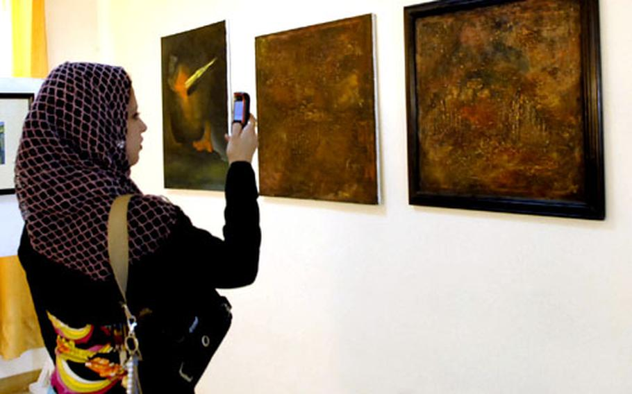 A woman takes a photo of a painting Wednesday at an art show in Baghdad's Dora neighborhood. The art show opened Wednesday, and organizers hope the return of culture to the neighborhood, which had been torn apart by sectarian violence, will help cement security gains.