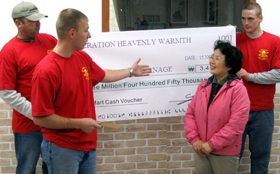 From left, soldiers Staff Sgt. Steven Presley, Sgt. 1st Class John Smith and Pvt. Matthew McDougall present a check for an E-Mart gift certificate to Aeshin Orphanage director Melody Yee. The soldiers from Fires Platoon, Bravo Battery, 1st Battalion, 38th Field Artillery, raised almost $4,600 from the Camp Casey community to help orphans through the winter.