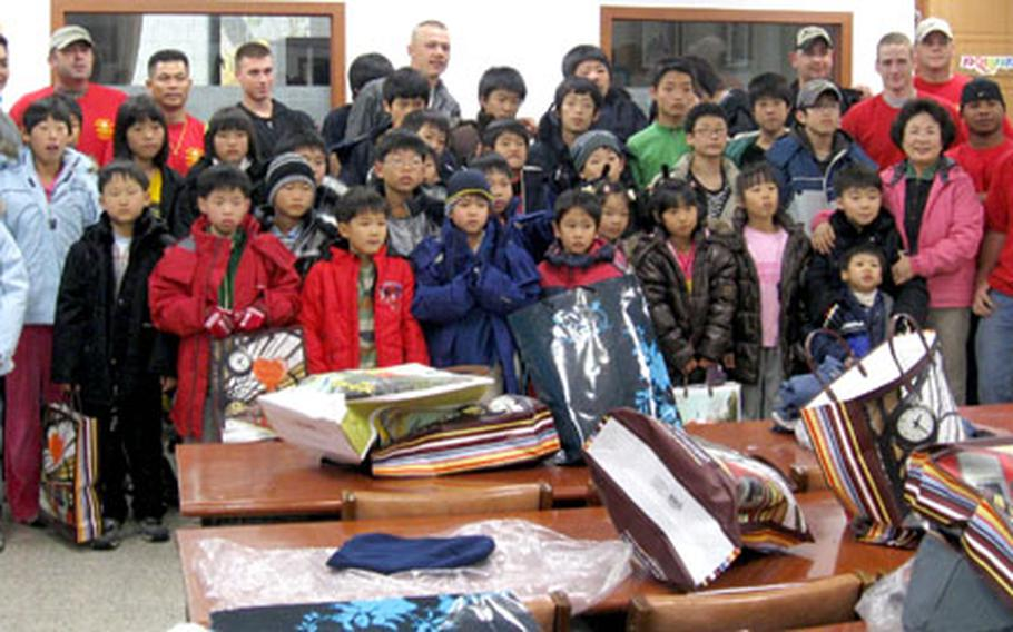 Soldiers from Fires Platoon, Bravo Battery, 1st Battalion, 38th Field Artillery, gather with residents of the Aeshin Orphanage in Dongducheon.