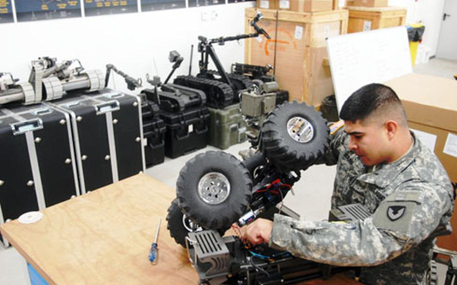 Sgt. Miguel Haro works on a robot at Hohenfels, Germany, on Monday. Most damage to the robots occurs because of operator error, Haro said.