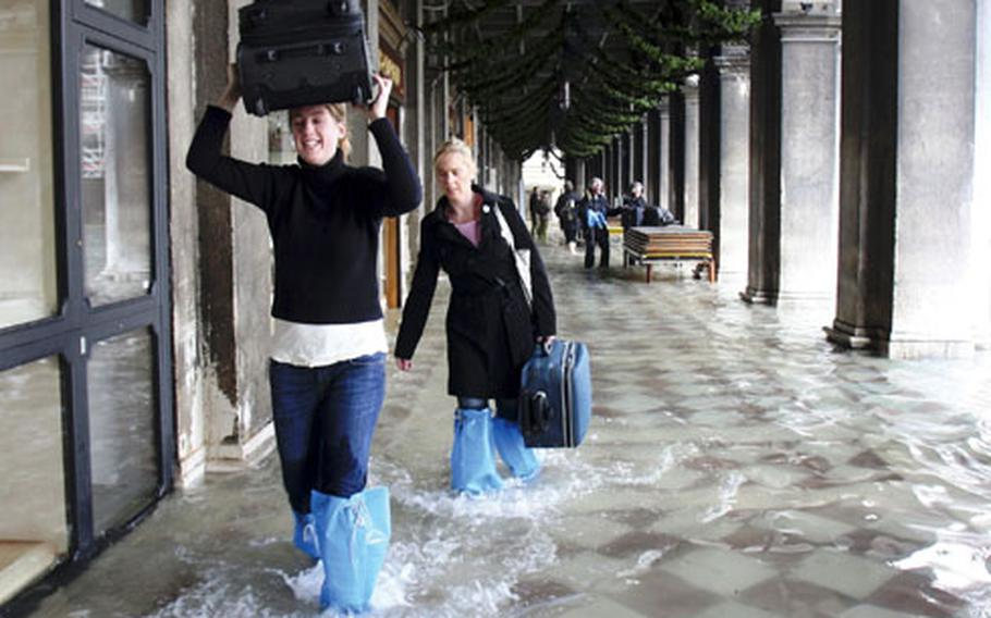 Tourists carry their luggage as they make their way through high water in Venice, Italy, on Monday. It's the worst flooding in Venice in more than 20 years.