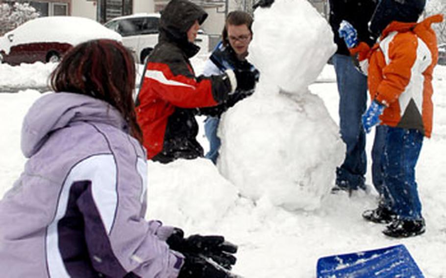 Rebekah Wilson, Kevin Godert, Geneva Nemier, Amber Wilson and Christopher Wilson, from left, build a snowman at Wetzel housing area in Baumholder