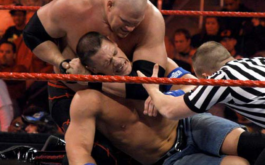 John Cena, center, tries to free himself from Kane's headlock. Cena has traveled to Iraq five times with the WWE Tribute to the Troops tour.
