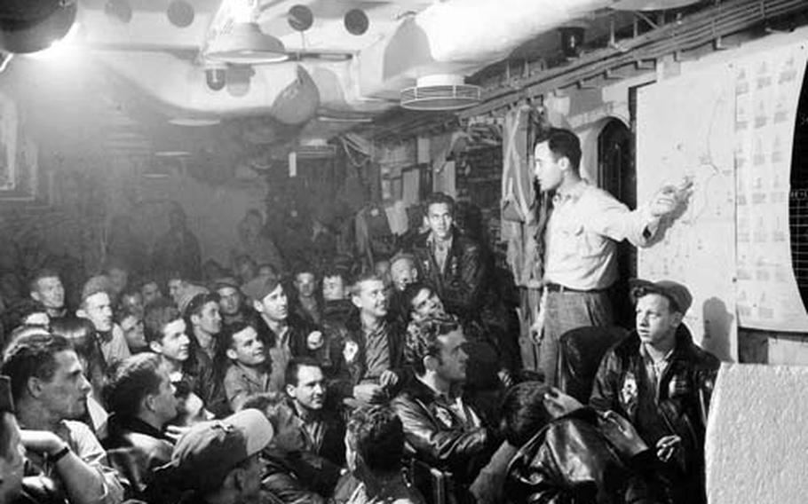"""J. Waite """"Slabo"""" Bacon, torpedo squadron intelligence officer, briefs pilots and crew in their ready room before a strike. The room was blown apart when Ogawa's plane crashed into the Bunker Hill."""
