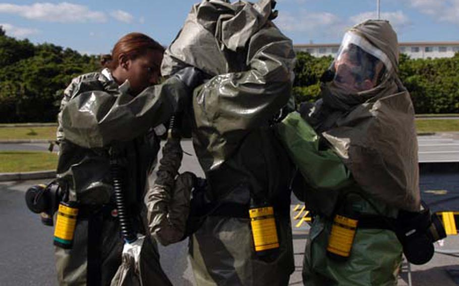 Senior Airman Jazmine Clark, left, Staff Sgt. Keneisha Fuller, center, and Staff Sgt. Jeanett Vielman, all of the 18th Medical Group, suit up for a decontamination drill Thursday at Kadena Air Base on Okinawa. The exercise involved cleaning up victims exposed to hazardous chemicals. Thousands of airmen in the 18th Wing were participating in emergency response drills as part of a weeklong Operational Readiness Exercise.