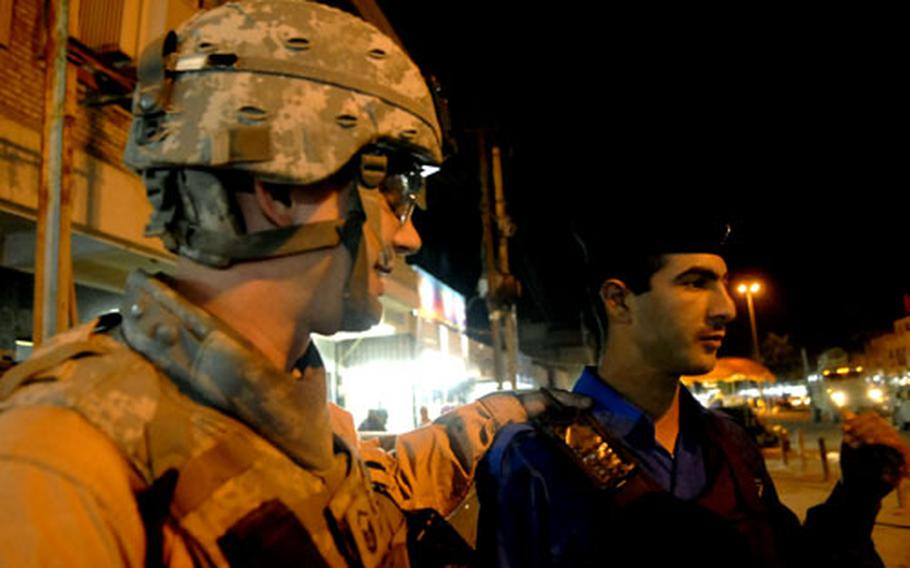 Air Force Master Sgt. Tom Daniels gives some pointers to an Iraqi Police officer during a joint patrol in south Baghdad.