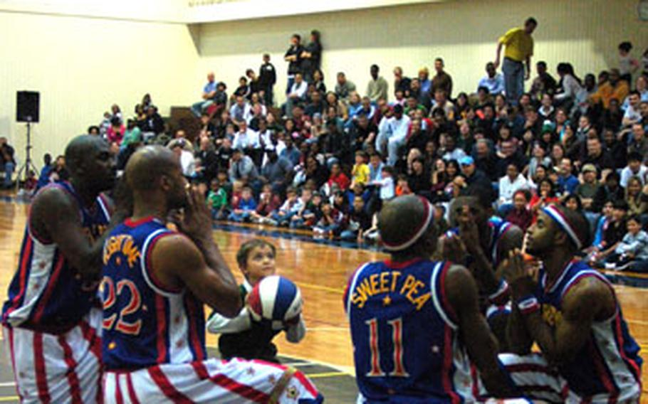 Members of the Harlem Globetrotters offer prayers as a young member of the audience prepares to take a shot Friday night Yokota Air Base's Samurai Fitness Center. The Globetrotters visited Yokota as part of their holiday tour of military bases throughout the Pacific.