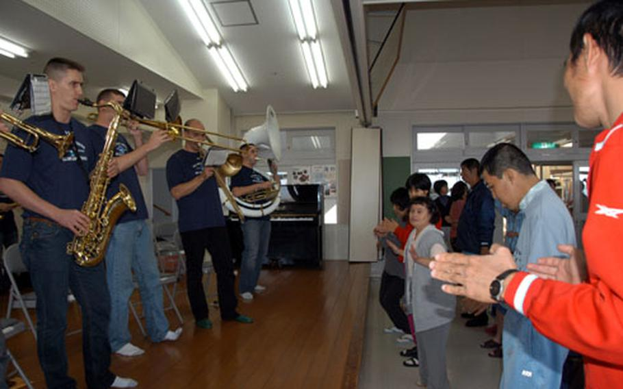 Twelve members of the the U.S. Army Japan Band perform as residents from the Takashihoen facility dance. The performance was the band's second at the facility for developmentally disabled adults.