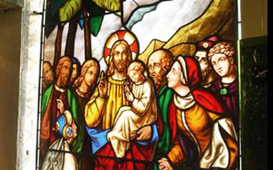 """Stained-glass works of art are pretty unremarkable until light is added to the mix, such as with """"Christ Blessing the Children,"""" a 19th-century work on display at The Stained Glass Museum."""