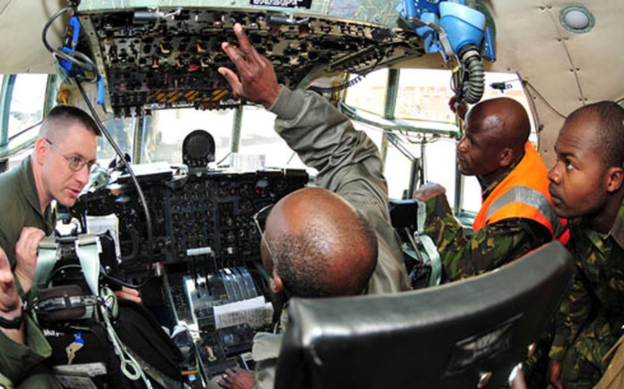 Master Sgt. James Pentergast, left, 37th Airlift Squadron C-130 flight engineer, shows the cockpit of one of the U.S. C-130s to members of the Botswana Defense Force.