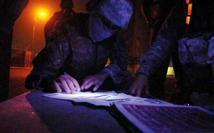 A masked interpreter translates some documents for an American patrol in Baghdad.