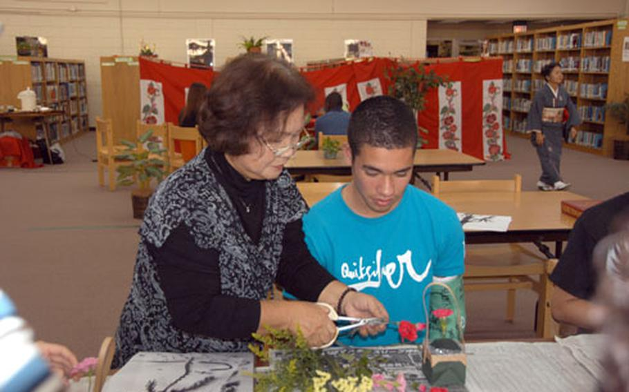 Instructor Sachiko Takaesu helps senior Danny Fisher, 17, cut carnations for a flower arrangement Thursday at Kubasaki High School. Fisher and classmates from his sociology class were learning Japanese flower arrangement, or ikebana, as part of a cultural activity day.
