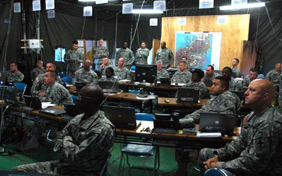 Members of the 8th Theater Support Command's forward command post conduct a briefing on Friday during the Yama Sakura exercise at Camp Asaka, Japan.