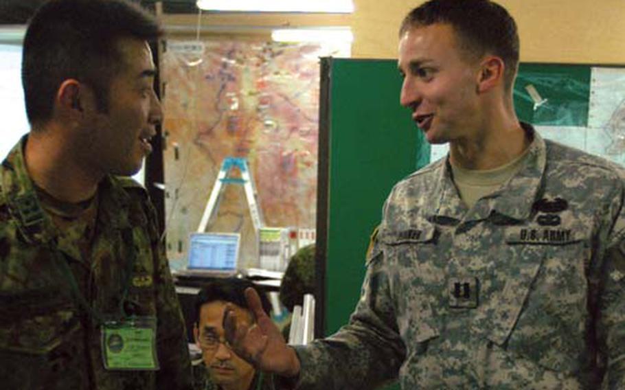 Japan Ground Self-Defense Foce Capt. Naoki Kobayashi, left, and U.S. Army Capt. Bryan Dunker chat Friday during the 2008 Yama Sakura exercise at Camp Asaka, Japan.