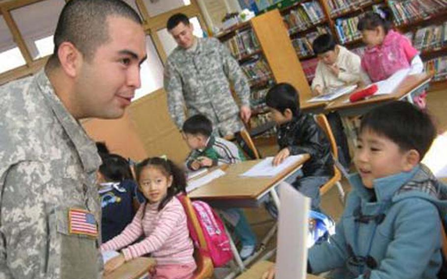 Soldiers stationed at Camp Carroll, South Korea, work with students at the Gwanho Elementary School near the base. Camp Carroll soldiers have been volunteering at the school since last year. Their efforts helped the small school remain open.