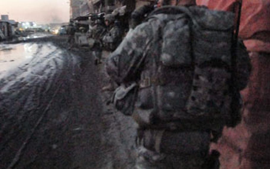 Staff Sgt. Christopher Dyer, a platoon sergeant with Company A, 1st Battalion, 6th Infantry Regiment, walks through the Jamilla market during a patrol Saturday night. The market was the scene of heavy fighting until soldiers built a wall that limited the movement of Mahdi Army members.