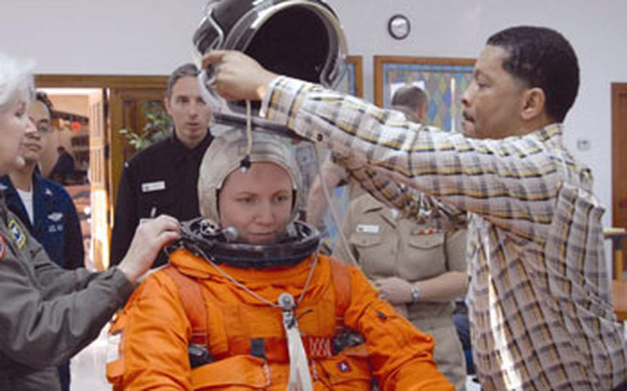 George Brittingham, member of a NASA training team, puts a spacesuit helmet on Lt. Lisa Steiner, a nurse at Naval Station Rota, during training class.