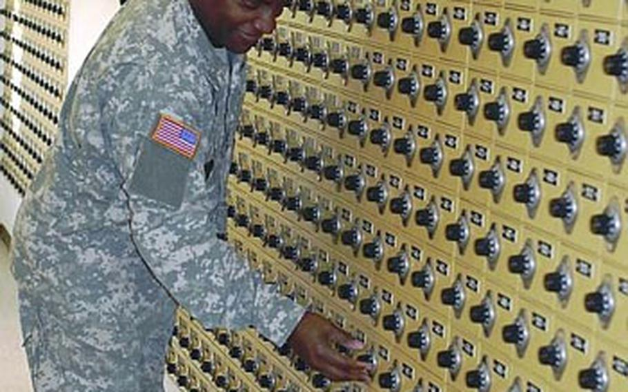 Army Master Sgt. Johnnie Davis with the 7th Civil Support Command checks his mail Monday at Daenner Kaserne in Kaiserslautern, Germany. A mistake at a U.S. Postal Service center in New York City is causing delivery delays in mail that was sent from the States to Europe in November.