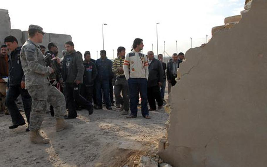 An American soldier monitors community project workers collecting their pay Monday at a patrol base on the border of Baghdad's Sadr City district. U.S. forces in the area are overseeing the program despite a trend toward turning funding responsibilities over to the Iraqis.