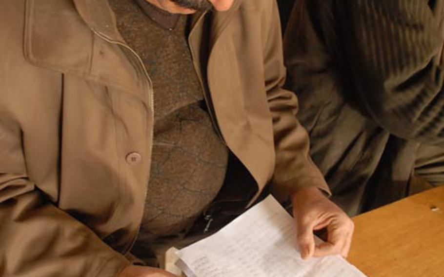Salim Malah al-Saadi, a supervisor who manages 50 community project workers, checks the name of one of the workers against a list while distributing their pay Monday at a patrol base on the border of Baghdad's Sadr City district.