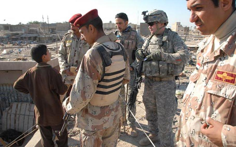 American and Iraqi troops check into reports of a weapons cache atop a building in Mahmudiyah on Tuesday.