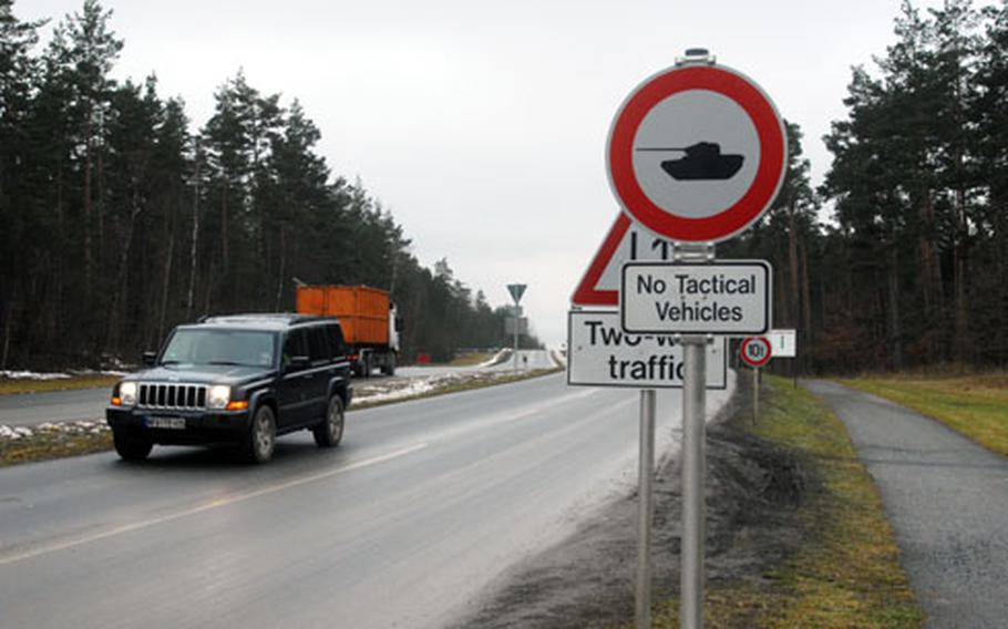A truck in the background travels on the tank trail which runs parallel to an ordinary on-post road in the foreground in Grafenwöhr, Germany. The tank trail connects the communities of Vilseck and Grafenwöhr, and some soldiers would like to be able to drive private automobiles on the trail to save travel times between the two bases.