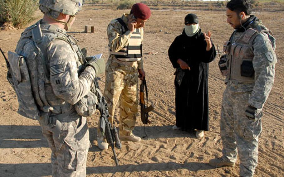 An Iraqi Army officer, along with Capt. Tom Smith and his interpreter, questions a woman during a raid Thursday on a farm that was believed to be harboring an al Qaida operative. The raid produced no captures despite evidence the wanted man had recently been on the property.