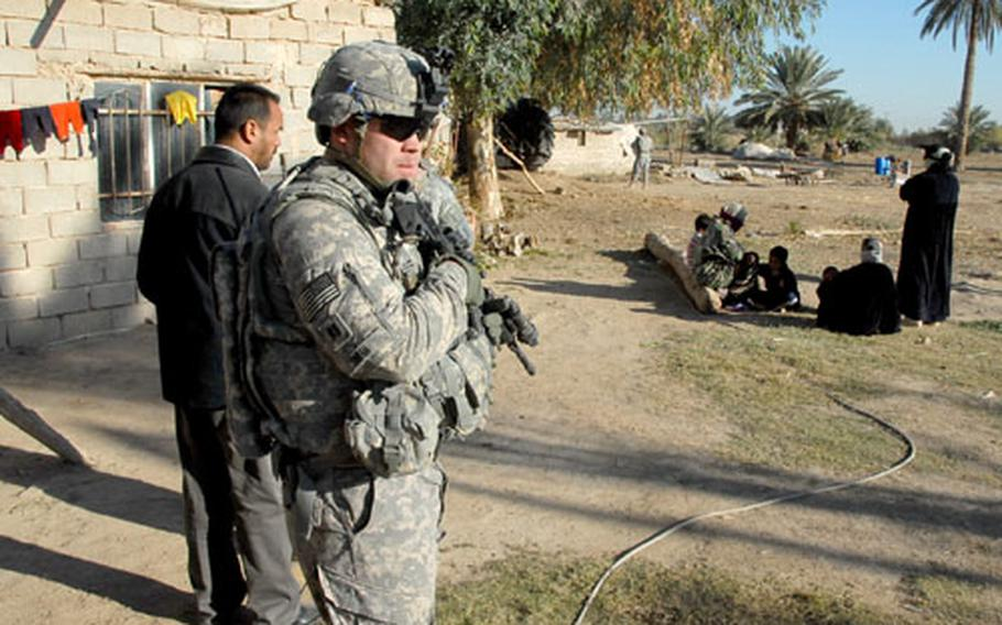 Capt. Tom Smith watches a group of women during a raid in the Mahmudiyah countryside Thursday. Intelligence reports said a wanted Al Qaeda operative and his bodyguards were staying at the farm but the women said only students and farmers had been there.