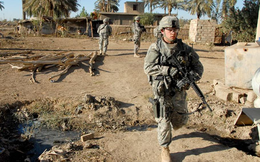 Second Lt. Kevin Mussman searches a farm where an al- Qaida operative was thought to be hiding Thursday. The wanted man is known for wearing a suicide vest and dressing like a woman to escape capture.