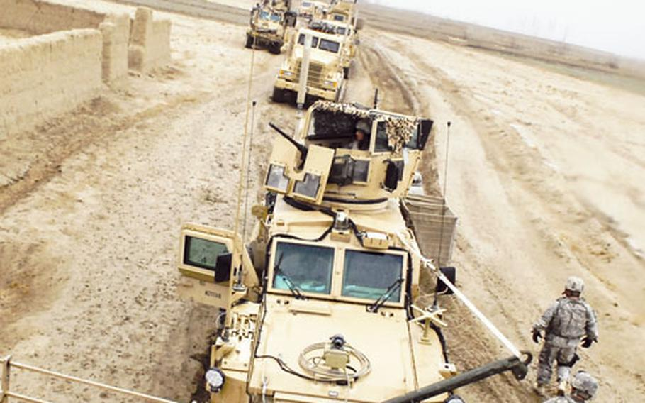 Route clearance vehicles lead a 60-vehicle supply convoy through the desert in Paktika province, Afghanistan. A sharp spike in roadside bombings this year has complicated the already difficult task of moving supplies across Afghanistan's rugged terrain.