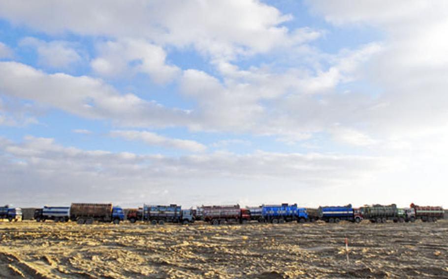 """A line of Afghan-driven """"jingle trucks"""" waits to leave a U.S. base in southeastern Afghanistan. The military depends on local transport to move fuel, but officers say the drivers are often inexperienced and understandably jittery on the dangerous rides."""
