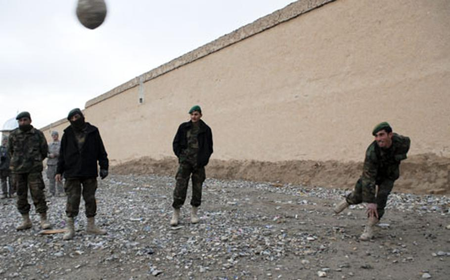 """During a break in a three-day convoy that covered roughly 60 miles, Afghan soldiers participate in the proto-Olympic sport of """"large rock tossing."""" The military relies on local trucking to move much of the fuel needed to run everything from generators and heaters to Humvees and armored vehicles."""