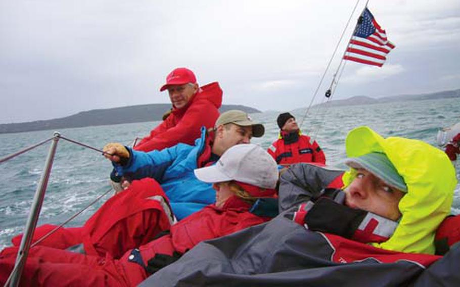 (From back to front) Navy Reservist Lt. Stuart Gold, Jan Chrypinski, Army Capt. Al Eckart, Navy Reservist Lt. Sandra Salvatori and Court Rawson gather on the high side of their vessel to keep it on keel during the Croatian Navy Cup and Christmas Regatta, a 28-nautical mile navigational run off the coast of Croatia.