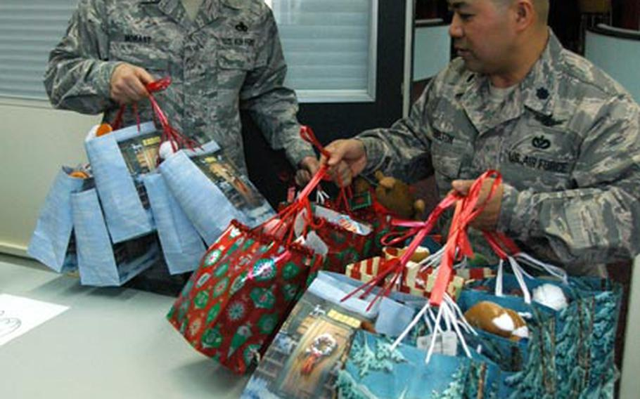 First Sgt. Kelly Morast, the 374th Civil Engineering Squadron first sergeant, and Lt. Col. Nam Shelton, commander of the 374th CES, pick up Project Elf gift bags Wednesday.